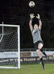 Goalie Meredith Gilleland leaps to make a save during girls soccer team practices at Milton High School on Friday, Jan. 17, 2020.