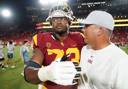 Southern California Trojans head coach  Clay Helton (right) and offensive tackle Austin Jackson (73) embrace after the game against the Fresno State Bulldogs at Los Angeles Memorial Coliseum. USC defeated Fresno State 31-23.