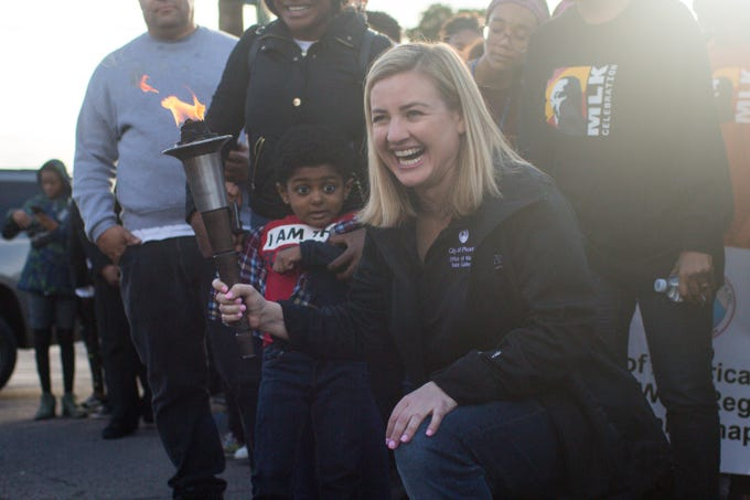 Phoenix Mayor Kate Gallego holds the torch at the beginning of the march as people begin on the annual MLK march from Pilgrim Rest Baptist Church to Hance Park on Monday, Jan. 20, 2020, in Phoenix.