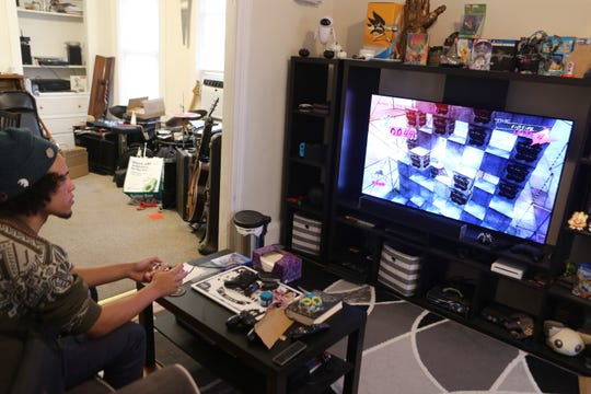 """Michael Davis in his living room playing """"Catherine,"""" the video game for which he traveled to Japan this week to compete in a tournament."""