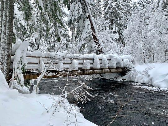 A snowy bridge crosses Salt Creek to begin the winter route to Diamond Creek Falls.