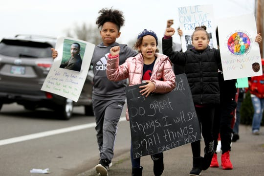 From left, Mehemiah Mendoza, 10, Elionnah Marchbanks, 6, and Elisha Marchbanks, 8, all of Salem, raise their fists during a march in celebration of Martin Luther King Jr. Day from McKay High School to the Willamette Town Center in Salem on Jan. 20, 2020.