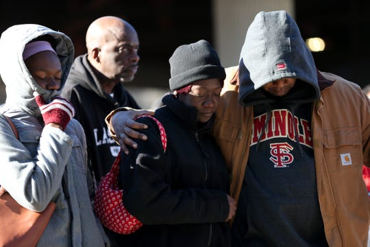 Shonda Williams, daughter of Darryl Steele and granddaughter of C.K. Steele, center, her daughter, left, and her boyfriend, Phillip Harvey, bow their heads in a prayer lead by Derek Steele, Williams' uncle at the Martin Luther King Jr. commemorative service at the C.K. Steele bus plaza Monday, Jan. 20, 2020.