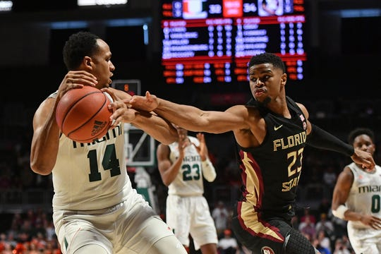 Jan 18, 2020; Coral Gables, Florida, USA; Florida State Seminoles guard M.J. Walker (23) knocks the ball from Miami Hurricanes center Rodney Miller Jr. (14) during the second half at Watsco Center. Mandatory Credit: Jasen Vinlove-USA TODAY Sports