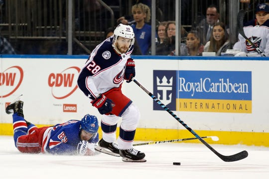New York Rangers right wing Pavel Buchnevich (89) hits the ice as Columbus Blue Jackets right wing Oliver Bjorkstrand (28) looks for his next move during the first period of an NHL hockey game, Sunday, Jan. 19, 2020, in New York. (AP Photo/Kathy Willens)