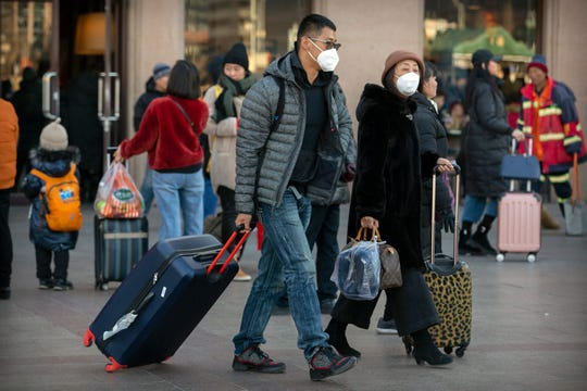 Travelers wear face masks as they walk outside of the Beijing Railway Station in Beijing, Monday, Jan. 20, 2020. China reported Monday a sharp rise in the number of people infected with a new coronavirus, including the first cases in the capital.
