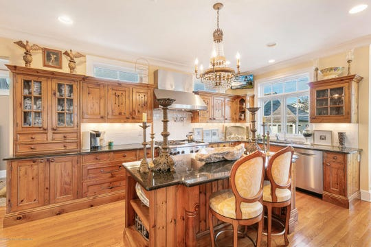 The custom kitchen features custom imported cabinetry from Great Britain with a center island.