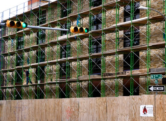 A worker prepares to climb down the scaffolding outside the Motis Building at North Second and Pine streets. The corner property is another major downtown project.