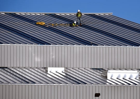 Workmen walk across the roof of a new building under construction at the Taylor County Expo Center. Work continues on a $55 million bond approved by residents to upgrade the facility in east Abilene.