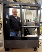 Clif McKenzie, CEO of Watson Furniture, looks over a storage cart being assembled on the factory floor in Poulsbo on Tuesday.