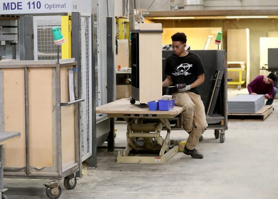 Builder Cedric Crowley assembles a storage unit at Watson Furniture in Poulsbo on Tuesday.