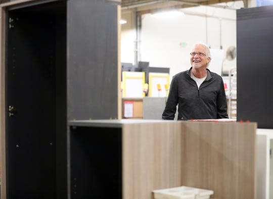 Clif McKenzie, CEO of Watson Furniture, is framed by office furniture in various stages of production as he gives a tour of the factory in Poulsbo on Tuesday.