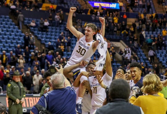 West Virginia Mountaineers players hold up West Virginia Mountaineers guard Spencer Macke (30) after beating the Texas Longhorns at WVU Coliseum.