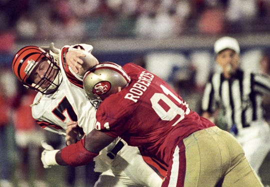 Jan 22, 1989; Miami, FL, USA; FILE PHOTO; San Francisco 49ers defensive end Larry Roberts (91) tackles Cincinnati Bengals quarterback Boomer Esiason (7) during Super Bowl XXIII at Joe Robbie Stadium. The 49ers defeated the Bengals 20-16. Mandatory Credit: Bob Deutsch-USA TODAY Sports