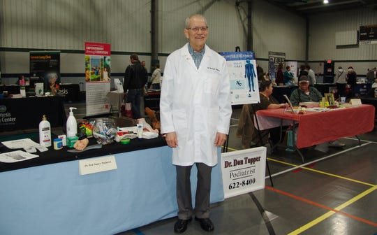 Dr. Don Tupper poses by his display at the expo.  He was one of 30 vendors offering health information at the annual event.