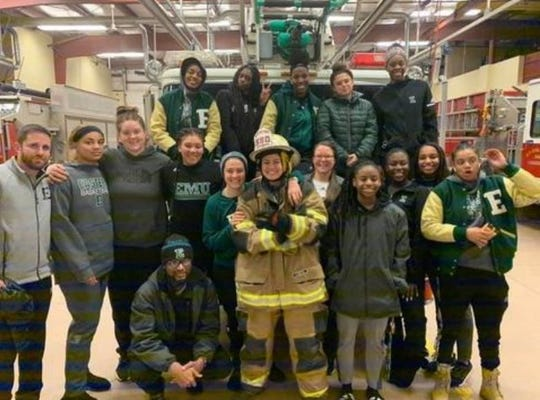 Sophomore guard Natalia Pineda wears a firefighter's gear Sunday surrounded by her Eastern Michigan University basketball teammates during their unscheduled visit to Girard's A.F. Dobler Hose & Ladder Co.
