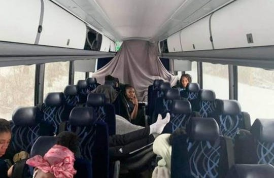 Members of the Eastern Michigan University women's basketball team relax while their bus is stranded on Tannery Road in Girard Pennsylvania.