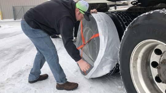 Advantage Fleet Parts Manager Rick Laug demonstrates the use of the AutoSock snow chain alternative in Coopersville Jan. 20.