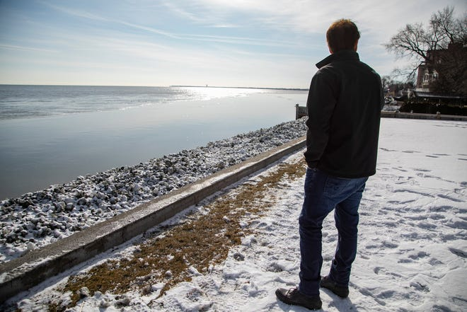 Harrison Township resident Joe Henninger stands near his breakwall on Lake St. Clair which was hit with  waves of sludge after heavy rains hit the metro Detroit area earlier this month.
