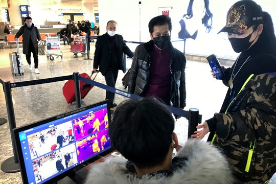 Travelers pass through a health screening checkpoint at Wuhan Tianhe International Airport in Wuhan in southern China's Hubei province, Tuesday.