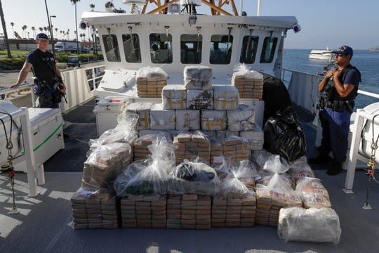 FILE - In this Aug. 29, 2019, file photo, members of the Coast Guard stand near seized cocaine in Los Angeles.