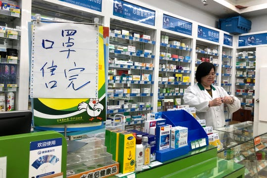 """Pharmacist Liu Zhuzhen stands near a sign reading """"face masks are sold out"""" at her pharmacy in Shanghai, Tuesday, Jan. 21, 2020."""