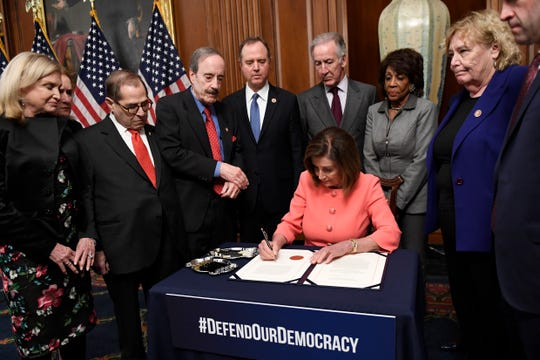 House Speaker Nancy Pelosi of Calif., signs the resolution to transmit the two articles of impeachment against President Donald Trump to the Senate for trial on Capitol Hill in Washington.Pelosi is surrounded by, from left, House Oversight and Government Reform Committee Chair Rep. Carolyn Maloney, D-N.Y., Rep. Sylvia Garcia, D-Texas, House Judiciary Committee Rep. Jerrold Nadler, D-N.Y., House Foreign Affairs Committee Chairman Rep. Eliot Engel, D-N.Y., House Intelligence Committee Chairman Adam Schiff, D-Calif., House Ways and Means Committee Chairman Rep. Richard Neal, D-Mass., House Financial Services Committee Chairwoman Maxine Waters, D-Calif., Rep. Zoe Lofgren, D-Calif., and Rep. Jason Crow, D-Colorado.