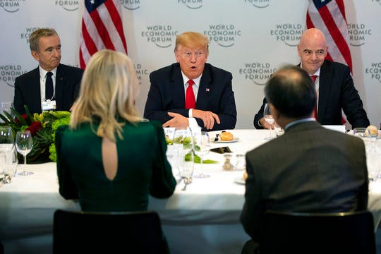 LVMH CEO Bernard Arnault, left, and FIFA president Gianni Infantino, right, listen as President Donald Trump speaks during a dinner with global business leaders at the World Economic Forum, Tuesday, Jan. 21, 2020, in Davos, Switzerland.