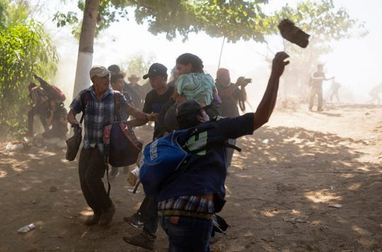 A Central American migrant throws a stone at Mexican National Guards after they crossed the Suchiate River from Guatemala to Mexico, on the riverbank near Ciudad Hidalgo, Mexico, Monday, Jan. 20, 2020.