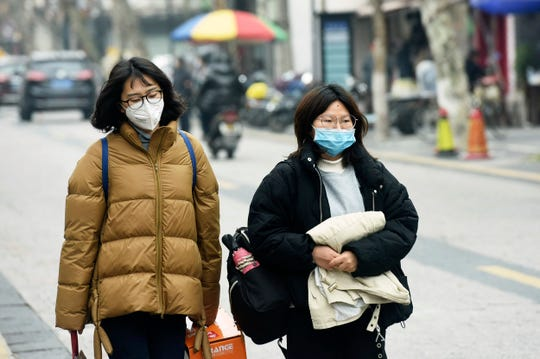 Women wear face masks as they walk down a street in Hangzhou in eastern China's Zhejiang province, Tuesday, Jan. 21, 2020. Face masks sold out and temperature checks at airports and train stations became the new norm as China strove Tuesday to control the outbreak of a new coronavirus that has reached four other countries and territories and threatens to spread further during the Lunar New Year travel rush.
