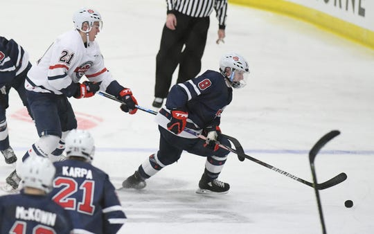 Team Knuble's Jake Sanderson, right, is checked by Carson Bantle of Team Gomez  at the All-American Game at USA Hockey Arena in Plymouth.