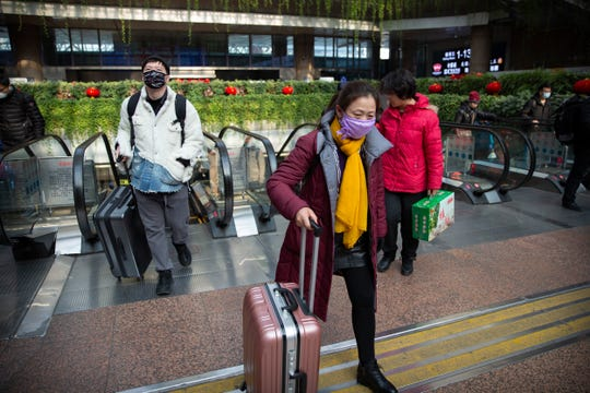 Travelers wear face masks as they arrive at Beijing West Railway Station in Beijing, Tuesday, Jan. 21, 2020. A fourth person has died in an outbreak of a new coronavirus in China, authorities said Tuesday, as more places stepped up medical screening of travelers from the country as it enters its busiest travel period.