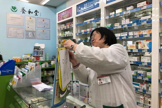 """Pharmacist Liu Zhuzhen hangs up a sign reading """"face masks are sold out"""" at her pharmacy in Shanghai, Tuesday."""