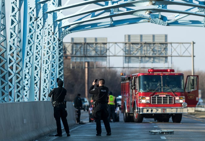Evansville Police Department officers take photos of the damage done to a small bridge on U.S. 41, north of Diamond Avenue, following a single-truck accident in Evansville, Tuesday afternoon, Jan. 21, 2020. All southbound lanes of U.S. 41 were closed and drivers were routed to the exit ramp at Fares Avenue.