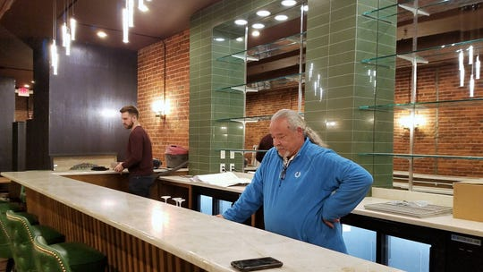 Managing partner Morgan Lemond, left and wine specialist Walter Edwards Jr. behind the mid-century style bar at Entwined.