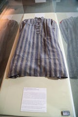 """A prison uniform is on display in the show. Bailey Rodgers, Adrian Sanchez, Abigail Winslow, Jordan Curtis, Kinsey Brown and Carey Walker worked alongside Melissa VandeBurgt, the head of archives, special collections and digital initiatives at FGCU's library, to put together """"To Life: The Liberation of Ravensbrück."""" The exhibit shares the stories of hope, compassion and perseverance to come out of the Ravensbrück concentration camp and to share the little-known story of the White Buses, a rescue operation undertaken by the Swedish Red Cross."""