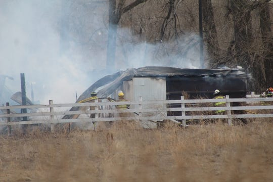 Firefighters douse hot spots at a workshop that burned Monday afternoon.