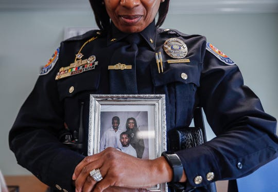 Newly appointed Southport Police Department assistant chief Lossie M. Davis poses with a family photo of her sons for IndyStar at Southport Police Department, Southport, Ind., Thursday, Jan. 16, 2020. Davis is the first woman and first African American woman to hold command staff position in the of the departments 180 year history.