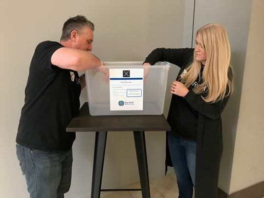 X Church Groups Pastor Steve Rauch (left) and outreach team leader Amanda Edmonds put a box outside of the church at the River Valley Mall for people to donate clothes for Fairfield Medical Center emergency room patients whose clothes may have been destroyed.