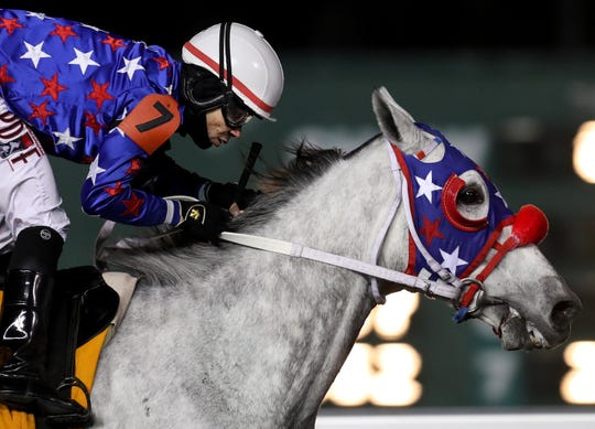 Gotsomemojo, with jockey Abel Lezcano, wins the first race at Turfway Park on a Thursday night.