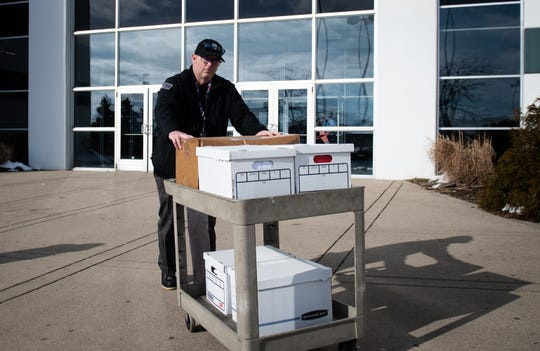 An investigator with the Office of the  Michigan Attorney General leaves Twistars Gymnastics Club in Dimondale, Michigan,  Tuesday, Jan. 21, 2020, with five boxes. Investigators also searched the home of John and Kathryn Geddert in Grand Ledge, Michigan.  [AP Photo/Matthew Dae Smith/Lansing State Journal]