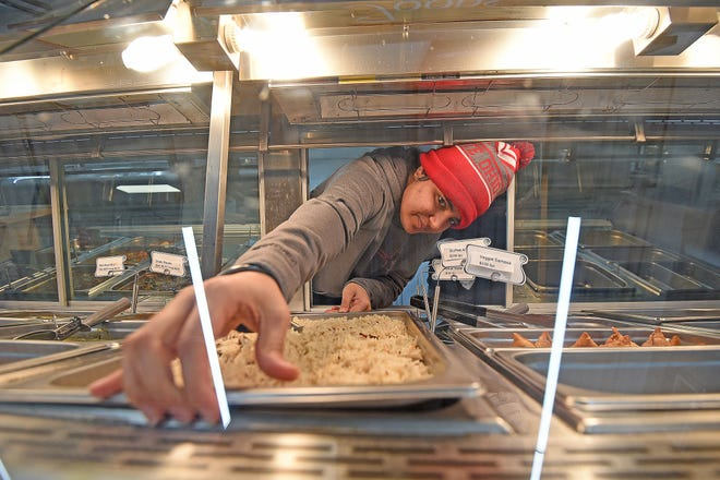 Avneet Kaur Bhullar stocks the new hot food section at KV Market on Tuesday morning.