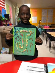 "Jadon Knox holds up artwork with the letter ""J"" illustrated on it at Aspire Hanley Elementary School."