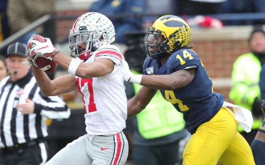 Ohio State Buckeyes receiver Chris Olave catches a touchdown against Michigan Wolverines safety Josh Metellus during the first half Saturday, Nov. 30, 2019, at Michigan Stadium.
