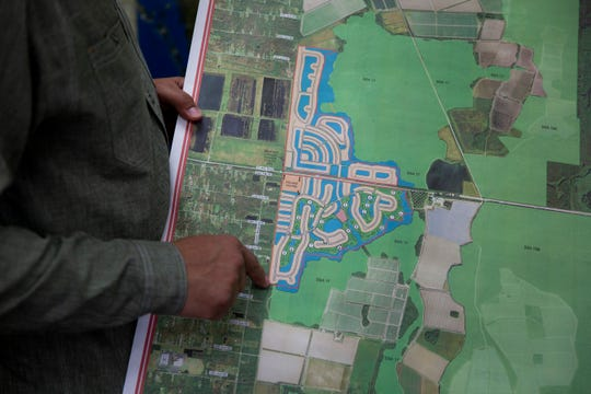 Christian Spilker, vice president of land management for Collier Enterprises, points to a map of the proposed Rivergrass Village near Oil Well Road on Monday, January 20, 2020.