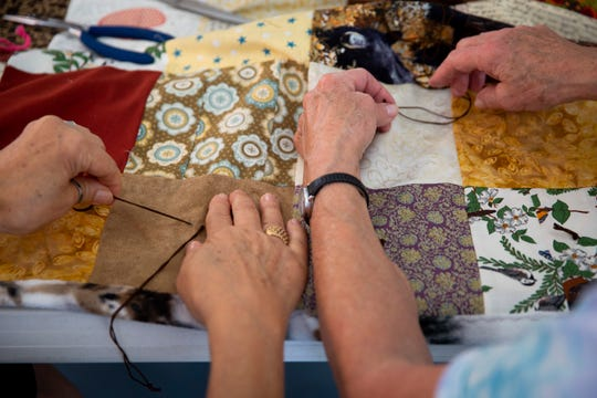 Denise Gunckle, left, and Mary Boardman, right, work on tying a quilt at Corkscrew Woodlands in Estero on Friday, January 17, 2020. The group makes quilts that are big enough to cover beds as well as smaller quilts for veterans in wheelchairs to cover their laps.