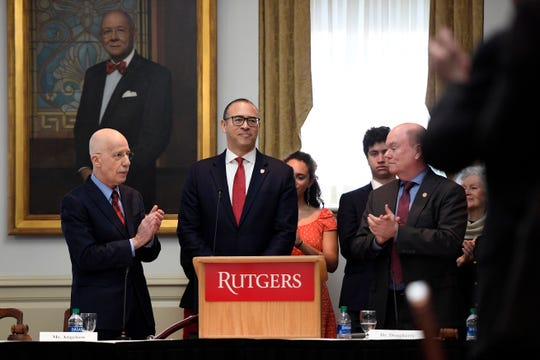 The Rutgers University Board of Governors applauds Jonathan Holloway, center, after electing Holloway to be the first non-white president of the university on Tuesday, Jan. 21, 2020, in New Brunswick.