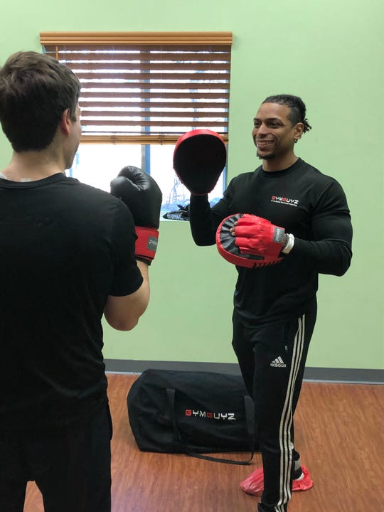 Matthew Sinclair, a physical therapist with GYMGUYZ of Bergen County and Northern Hudson, helps a client train.