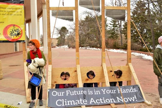 Climate activists place children in a model of a guillotine during a protest outside the New Mexico Statehouse before the start of the New Mexico legislative session in Santa Fe, N.M. on Tuesday, Jan. 21, 2020. New Mexico's Democrat-led Legislature is looking for new ways to bolster a lagging public education system and open up new economic opportunities by legalizing recreational marijuana and providing tuition-free college education, as a 30-day legislative session began Tuesday.