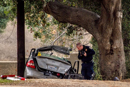 An officer with the California Highway Patrol's (CHP) Multidisciplinary Accident Investigation Team (MAIT) investigates the scene of a deadly crash in the Temescal Valley, south of Corona, Calif., Monday, Jan. 20, 2020. A Southern California driver intentionally rammed a Toyota Prius with several teenage boys inside, killing a few and injuring a few others before fleeing, authorities said Monday.